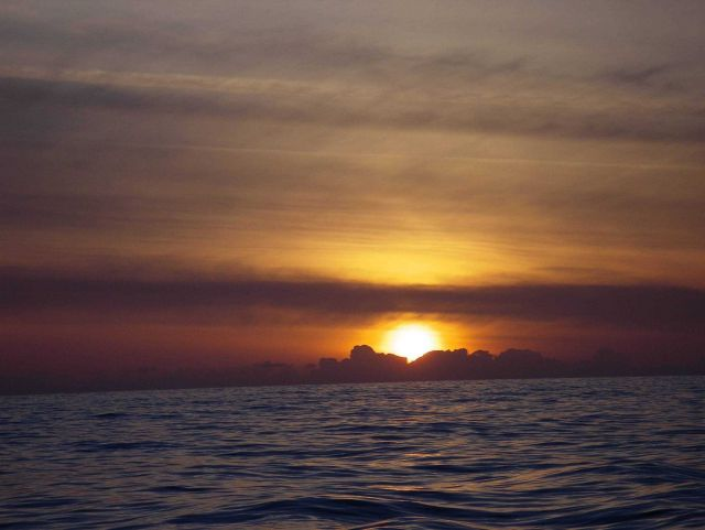 Sun setting over clouds on the ocean. Picture