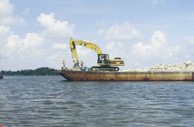 Barge and crane preparing to unload rock. Picture