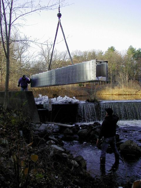 The crane lowers the first section into place, it is just about to be dropped into the notched dam. Picture