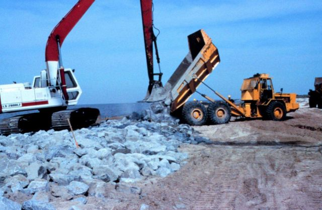 A large crane places rock in the dump truck at the construction site. Picture