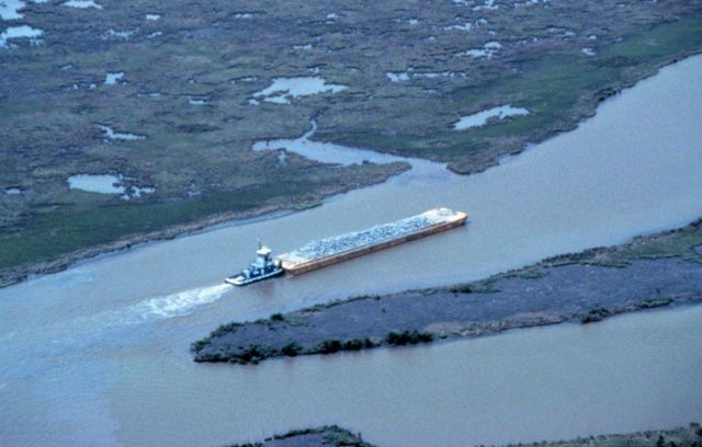 An aerial view of the tug pushing a barge load of rock up Locust Bayou. Picture