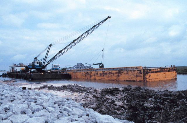 A barge-mounted crane loading rock at the construction site. Picture