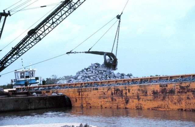 A barge mounted crane loads rock at the construction site. Picture