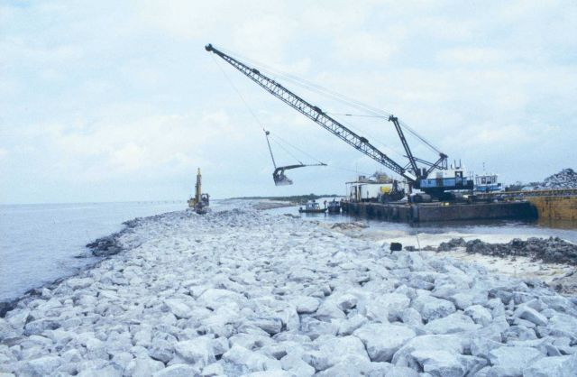 A barge-mounted crane loads rock which will be placed to stabilize shoreline erosion. Picture