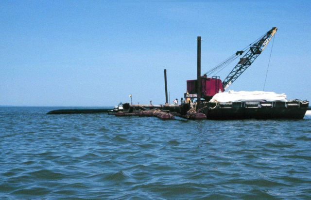 A barge with a crane is filling a geotube, in the background of the image. Picture