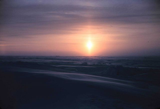 A sun pillar forms as the sun rises over the Arctic plain Picture