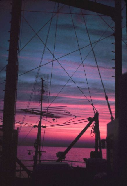ALBATROSS IV rigging and antennas superimpose geometric patterns on sunset. Picture