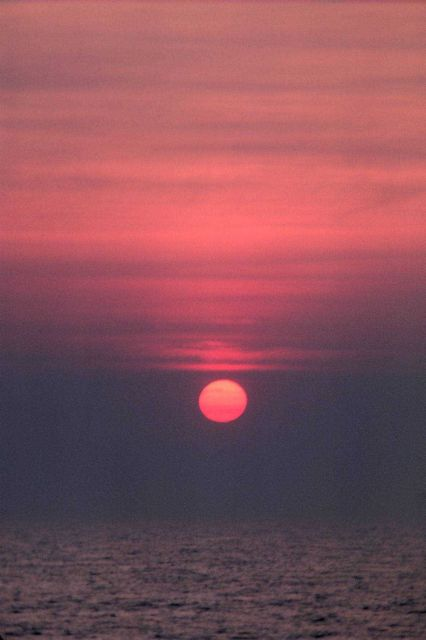 Sun as an orange sphere setting over the ocean. Picture