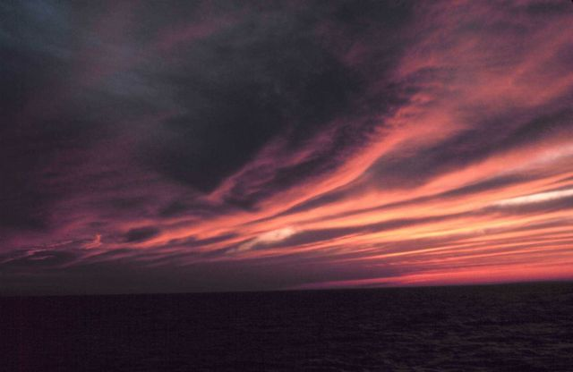 Parallel cloud bands illuminated by sun setting over the ocean. Picture