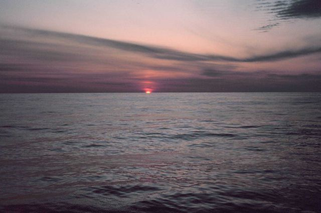 Sun peeking over the oceanic horizon at sunrise Picture
