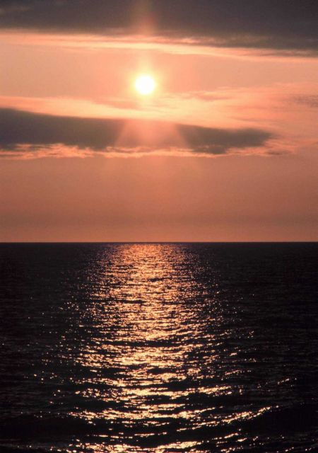 A streak of orange sunlight reflecting off the ocean at sunrise. Picture