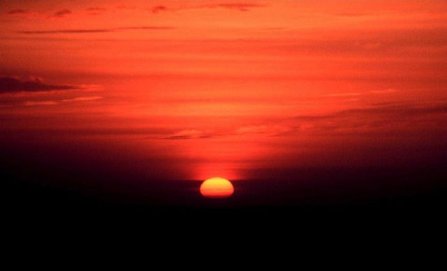 Sun approaching the horizon as the bottom limb is becoming obscured by far distant clouds. Picture