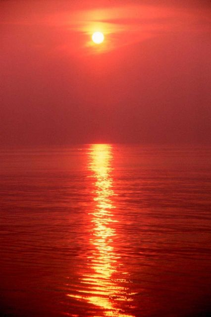 Orange sky and orange sea with a pillar of light reflecting off the ocean. Picture