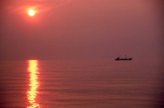 A small coastal freighter plying its way through a placid sea at sunset. Picture