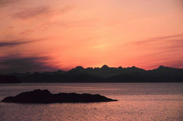 An islet in the foreground and mountains sharing the vista with a peach-hued sunset. Picture