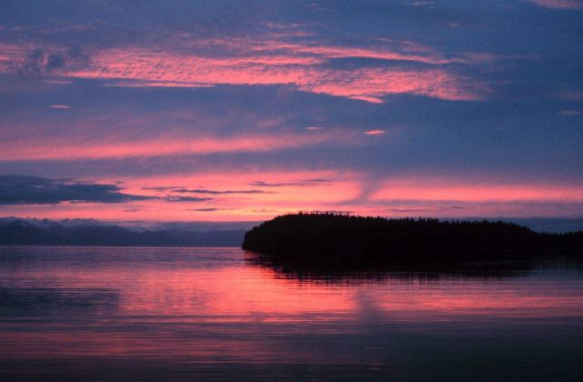 What a grand sunset! Mountains, an island and placid waters reflecting pink sky and clouds. Picture