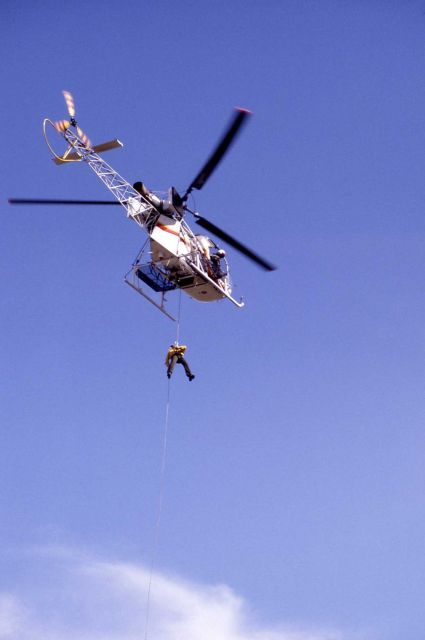 Helitack crew member repelling beneath helicopter near Mammoth Picture