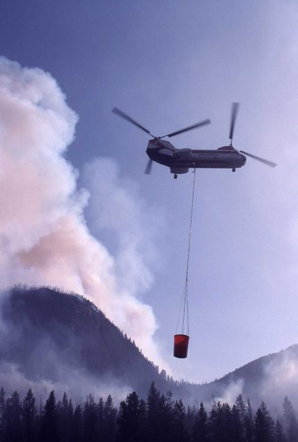 Single Vertol helicopter filling bucket above Madison River Picture