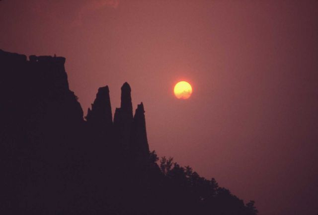 Smokey orange sunset with silhouetted cliff Picture
