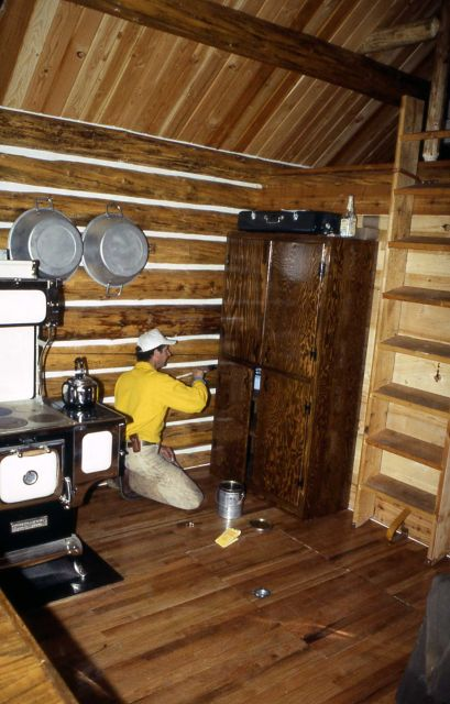 Maintenance worker finishing the cupboards at the Sportsman Lake cabin Picture