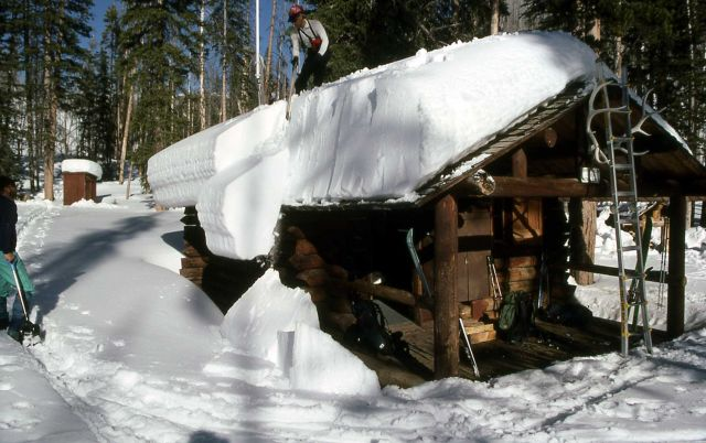 Ranger Brian Chan clearing roof of Upper Miller Creek cabin Picture