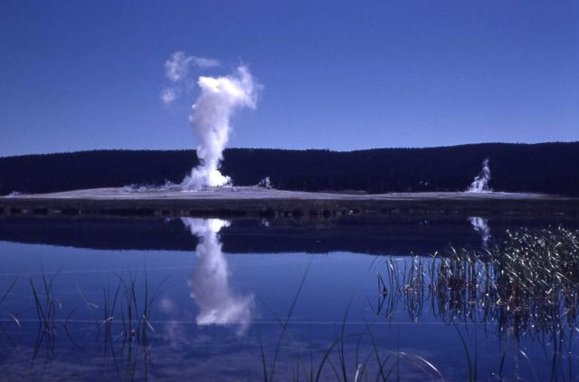 Distant view of Fountain Geyser with its reflection in pool - Midway & Lower Geyser Basin Picture