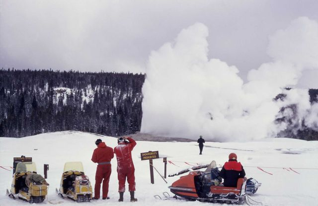 Snowmobiles & Old Faithful geyser in winter Picture