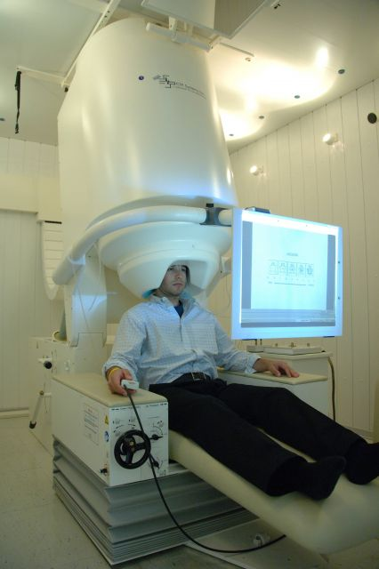 MEG scanner with patient doing task. Picture