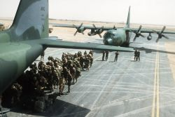 Troops of the U.S. Army's XVIII Airborne Corps wait to board a C-130 Hercules transport aircraft Photo