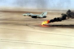 Navy F-14 - A Navy F-14 Tomcat flying over a burning oil field in Kuwait Photo
