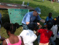 Volunteer show children about fishing equipment Photo