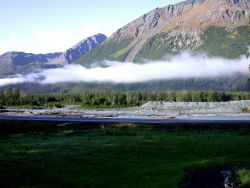 A ribbon of cloud separates mountain and valley Photo