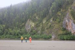 Canoe trekkers stop along the Yukon River between the Dalton Highway and Ruby to view lichen (orange material) covered rock outcrop. Photo