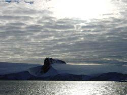 An angular mountain peak looking like the prow of a ship seemingly cuts through an Antarctic Peninsula ice field. Photo