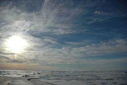 Midnight sun, melting Arctic ice, open leads, and cirrus clouds. Photo