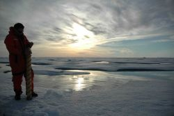 Rolf Gradinger is silhouetted by the Arctic sun while collecting an ice core. Photo
