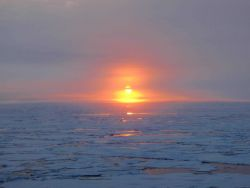 Sun reflecting off open water between ice floes Photo