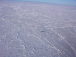 Pressure ridges, hummocks, and the frozen remains of a melt pond in the middle of the image. Photo