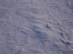 Multi-year ice with patterns caused by collisions, freezing and refreezing, and wind patterns caused by ablation and wind-sculpted snow. Photo