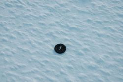 Camera lens camp showing scale of mini-hummocks on ice surface at Ice Camp. Photo