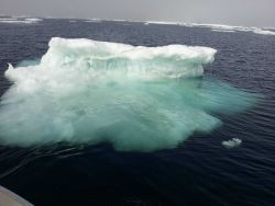 A small ice berg with its greater mass of ice visible below the surface. Image