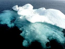 A small ice berg with its greater mass of ice visible below the surface. Photo