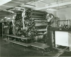 Coast and Geodetic Survey pressmen in action on a Harris press. Photo