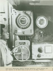 Chief Radio Technician, Ricardo Vendura, operating a depth recorder and monitoring a gyro repeater in the radio room of the U Photo