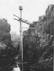 Tide gauge and staff erected in the Aleutian Islands. Photo