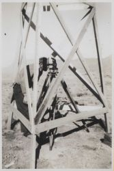 Charlie Bowman using a collimator to locate the center of the tripod which will support the theodolite on a 20-foot observing stand. Photo