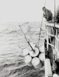 Placing marker buoys in water, purpose not noted on photograph. Photo