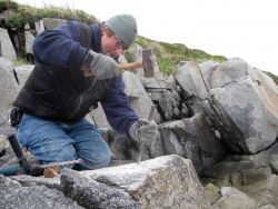 Starting a drill hole with hammer and chisel for placing a survey mark. Photo