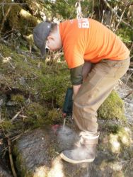 Using a power drill to drill a hole for placing a survey mark. Photo