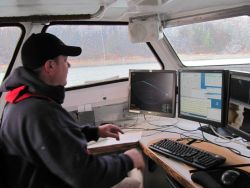 Hydrographic survey technician monitoring sonar. Photo